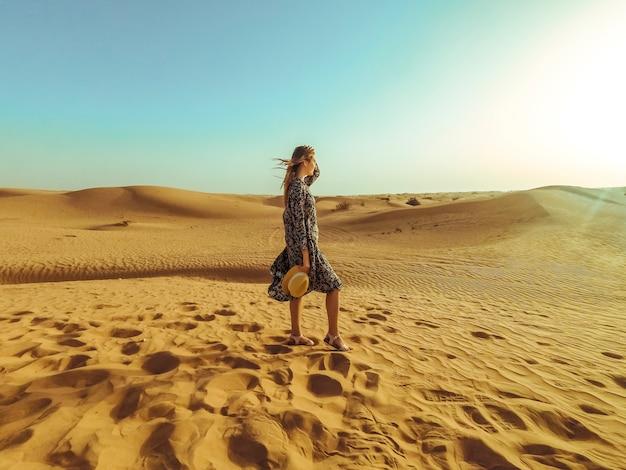 Jonge mooie vrouw in lange jurk en met een hoed in het midden van de woestijn van dubai met zonlicht
