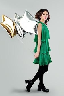 Jonge mooie vrouw in lente groene jurk met ballonnen