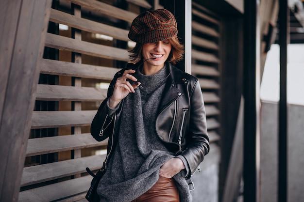 Jonge mooie vrouw in leren jas buiten de straat