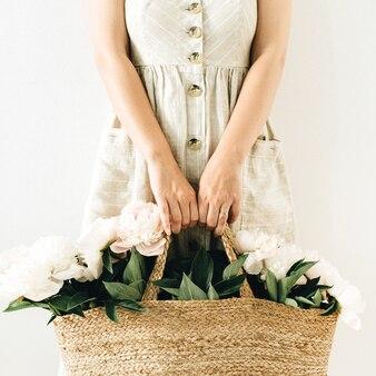 Jonge mooie vrouw in linnen jurk met strozak met witte pioenroos bloemen op wit oppervlak