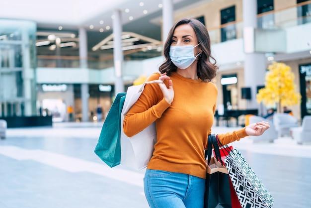 Jonge mooie vrouw in medisch veiligheidsmasker met boodschappentassen loopt op zwarte vrijdag in het winkelcentrum