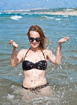 Jonge mooie vrouw in oceaan die waterplonsen maakt
