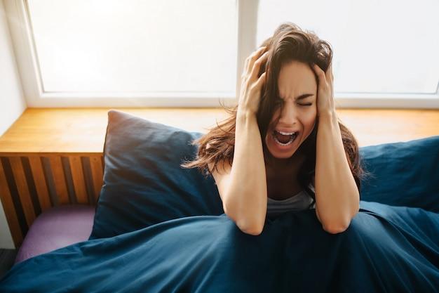 Jonge mooie vrouw in ochtendbed thuis. ga zitten en houd uw handen op het hoofd. schreeuw vanwege pijn en stress.
