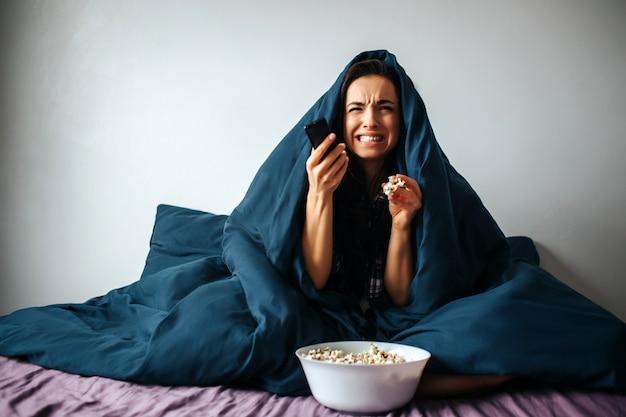 Jonge mooie vrouw in ochtendbed thuis. huilen onder deken. schakelen tussen tv-kanalen met afstandsbediening. houd wit weefsel in de hand om te huilen.