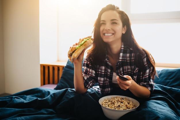 Jonge mooie vrouw in ochtendbed thuis. kijk tv of film en gebruik de afstandsbediening. broodje en popcorn eten.
