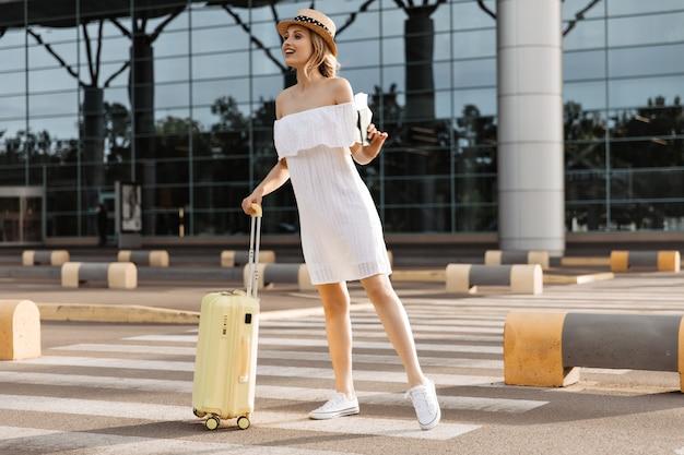 Jonge mooie vrouw in oversized witte jurk kijkt in de verte, houdt gele koffer en paspoort vast