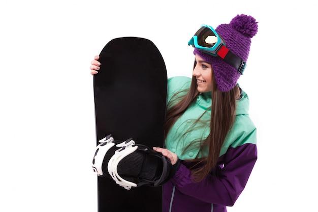 Jonge mooie vrouw in paarse ski jas en bril houden snowboard