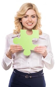 Jonge mooie vrouw in pak puzzelstukje houden.