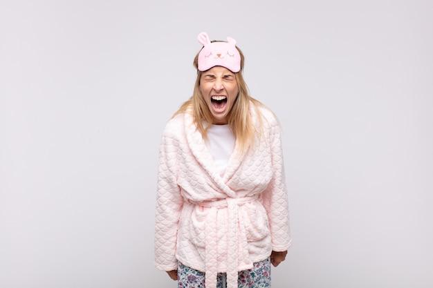 Jonge mooie vrouw in pyjama, agressief schreeuwend, erg boos, gefrustreerd, woedend of geïrriteerd, nee schreeuwend
