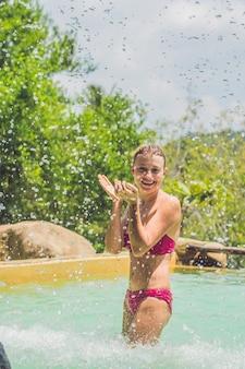 Jonge mooie vrouw in rode bikini in het zwembad van het waterpark omgeven door vele spatten