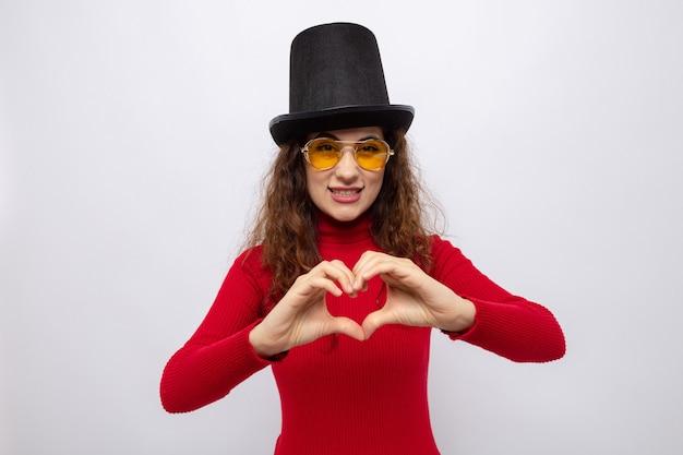 Jonge, mooie vrouw in rode coltrui in cilinderhoed met een gele bril die er vrolijk uitziet en een hartgebaar maakt met vingers