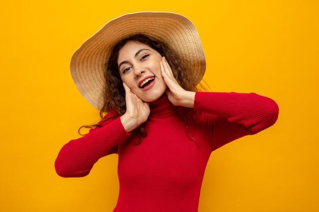 Jonge mooie vrouw in rode coltrui in zomerhoed, blij en positief glimlachend vrolijk staande op oranje