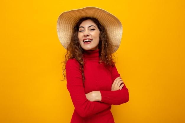 Jonge mooie vrouw in rode coltrui in zomerhoed die er gelukkig en vrolijk uitziet en breed glimlacht
