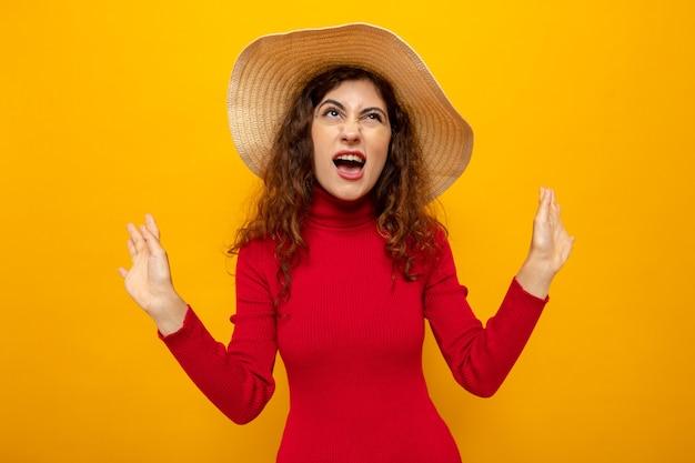 Jonge mooie vrouw in rode coltrui in zomerhoed die geïrriteerd en geïrriteerd opkijkt terwijl ze op oranje staat