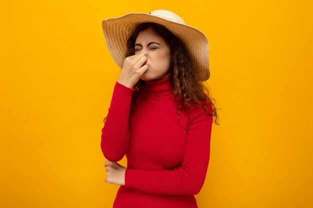 Jonge mooie vrouw in rode coltrui in zomerhoed die neus sluit met vingers die aan stank lijden