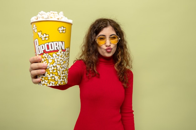 Jonge, mooie vrouw in rode coltrui met een gele bril die een emmer popcorn vasthoudt en vrolijk glimlacht op groen