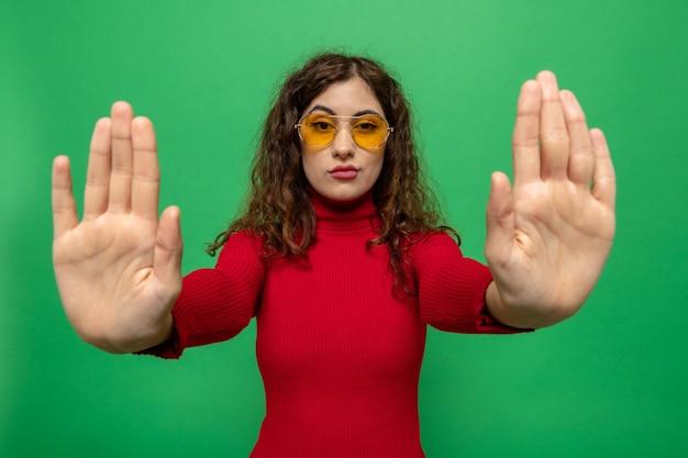 Jonge, mooie vrouw in rode coltrui met een gele bril die met een serieus gezicht kijkt en een stopgebaar maakt met de handen