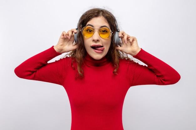 Jonge mooie vrouw in rode coltrui met koptelefoon met een gele bril die er gelukkig en vrolijk uitziet en tong uitsteekt terwijl ze geniet van favoriete muziek