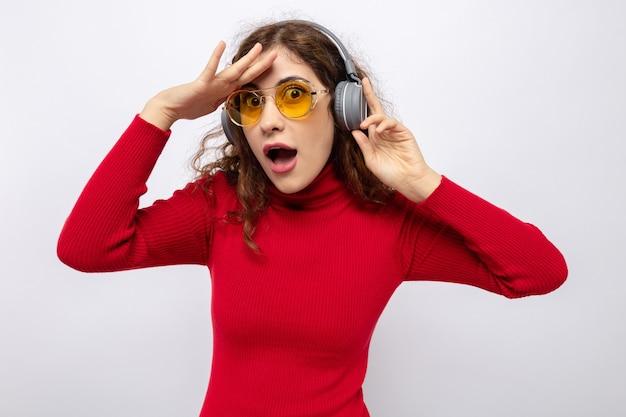 Jonge mooie vrouw in rode coltrui met koptelefoon met gele bril die verbaasd en verrast kijkt met de hand over haar voorhoofd