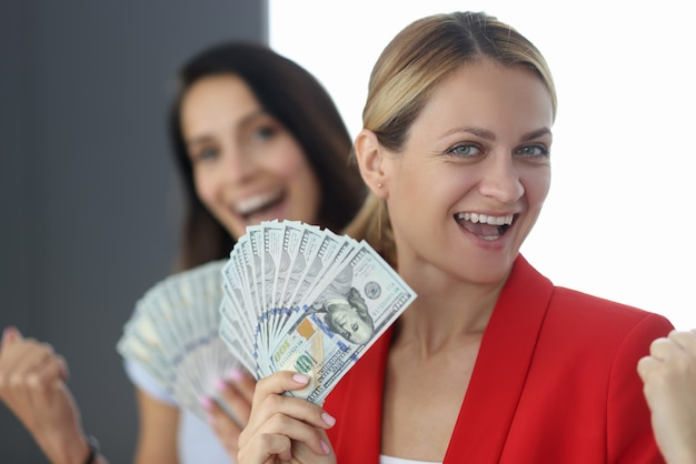 Jonge mooie vrouw in rode jas houdt contant geld portret op de achtergrond van de partner. ontwikkelingsconcept voor kleine bedrijven.