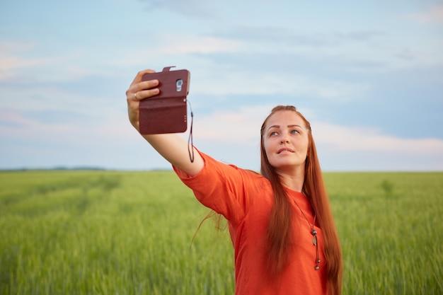 Jonge mooie vrouw in rode jurk en rood haar, neemt 's avonds een selfie op de telefoon in het groene tarweveld