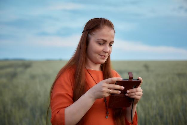 Jonge mooie vrouw in rode jurk met rood haar. bekijk uw foto's op uw telefoon en staat 's avonds bij zonsondergang in een groen tarweveld. moderne digitale technologie.