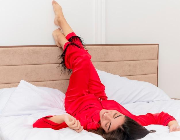 Jonge mooie vrouw in rode pyjama tot op bed rusten op zachte kussens met verhoogde benen gelukkig en positief genieten van weekend in slaapkamer interieur op lichte achtergrond