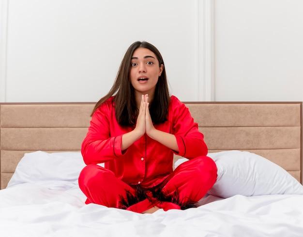 Jonge mooie vrouw in rode pyjama zittend op bed handpalmen bij elkaar houden zoals bidden of namaste gebaar emotionele en bezorgd in slaapkamer interieur op lichte achtergrond