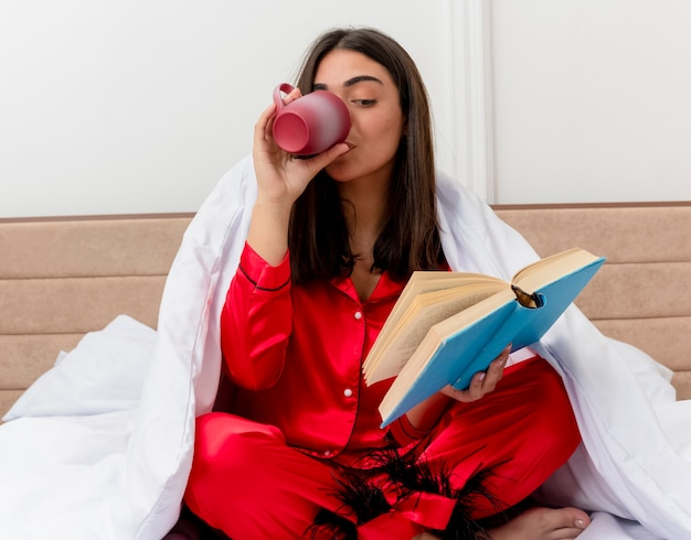 Jonge mooie vrouw in rode pyjama zittend op bed inwikkeling in deken met boek koffie drinken in slaapkamer interieur op lichte achtergrond