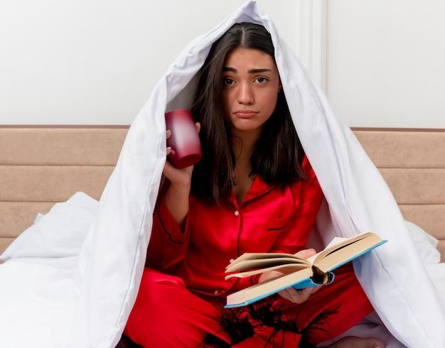 Jonge mooie vrouw in rode pyjama zittend op bed inwikkeling in deken met kopje koffie en boek camera kijken met droevige uitdrukking in slaapkamer interieur op lichte achtergrond