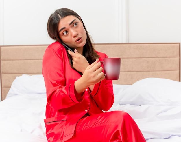 Jonge mooie vrouw in rode pyjama zittend op bed met kopje koffie praten op mobiele telefoon op zoek verward in slaapkamer interieur op lichte achtergrond