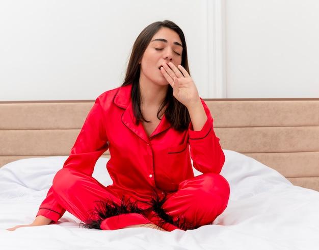 Jonge mooie vrouw in rode pyjama zittend op bed vermoeidheid voelen na werkdag geeuwen wil slapen in slaapkamer interieur op lichte achtergrond