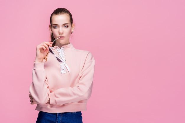 Jonge mooie vrouw in roze geïsoleerde sweater en zonnebril