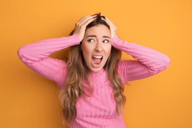 Jonge, mooie vrouw in roze top die gefrustreerd schreeuwt om wild te worden en haar haren over oranje trekt