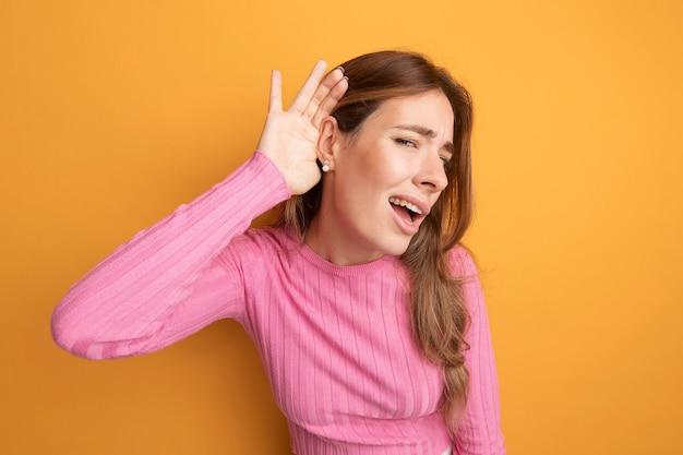 Jonge mooie vrouw in roze top die hand over haar oor houdt en naar roddels probeert te luisteren