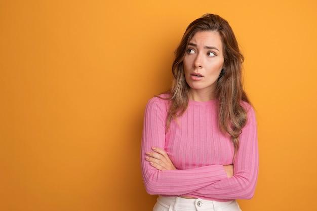 Jonge mooie vrouw in roze top die opzij kijkt, bezorgd en verward over oranje staat