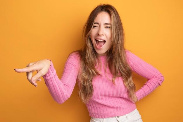Jonge, mooie vrouw in roze top die opzij kijkt, gelukkig en vrolijk, wijzend met de wijsvinger naar iets