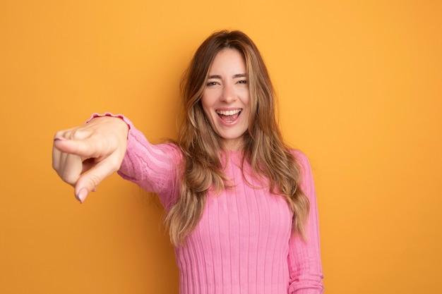 Jonge mooie vrouw in roze top kijken camera blij en opgewonden glimlachend