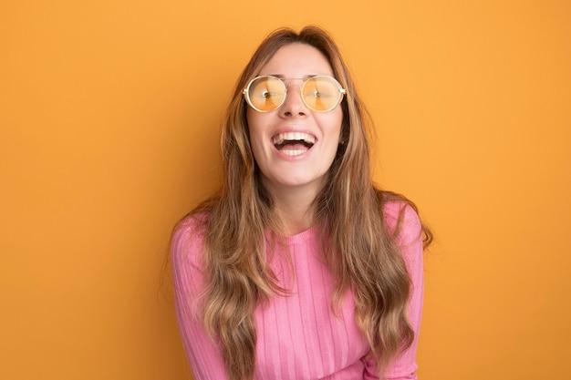 Jonge mooie vrouw in roze top met een bril, blij en vrolijk lachend