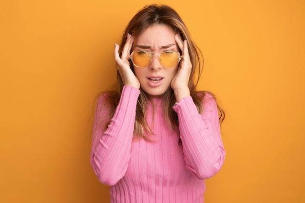 Jonge mooie vrouw in roze top met een bril die er onwel uitziet en haar slapen aanraakt met hoofdpijn die over oranje staat