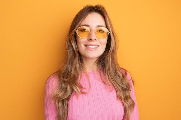 Jonge mooie vrouw in roze top met een bril die naar de camera kijkt en vrolijk glimlacht