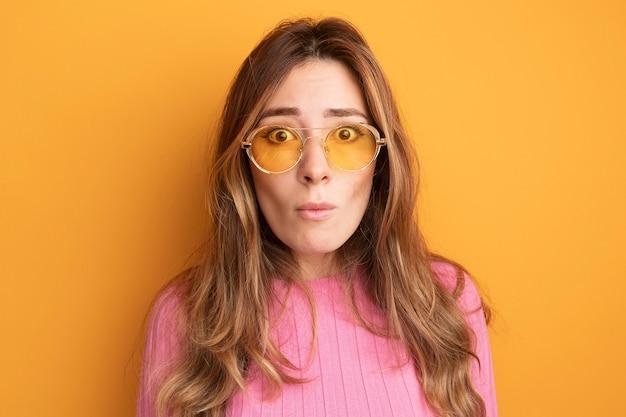 Jonge mooie vrouw in roze top met een bril die naar de camera kijkt, verrast en verbaasd staat over oranje