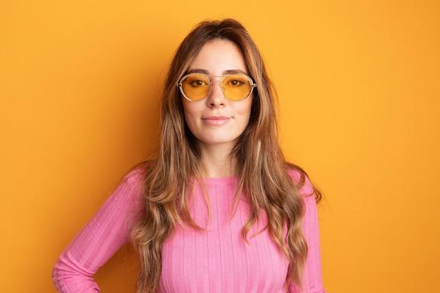 Jonge mooie vrouw in roze top met een bril die naar een camera kijkt die zelfverzekerd glimlacht en over oranje staat