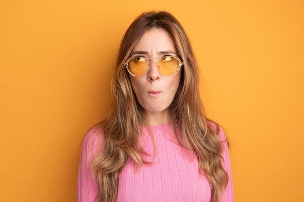 Jonge, mooie vrouw in roze top met een bril die verbaasd opkijkt terwijl ze over oranje staat