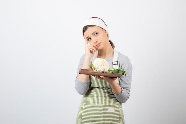 Jonge mooie vrouw in schort met bord bloemkool en denken?
