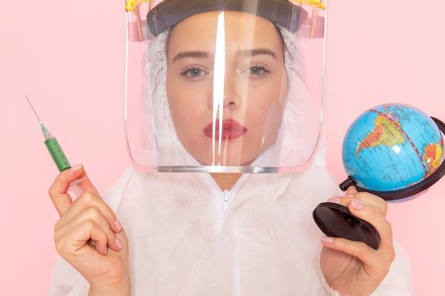 Jonge mooie vrouw in speciaal wit pak dragen van beschermende helm injectie wereldbol op roze te houden