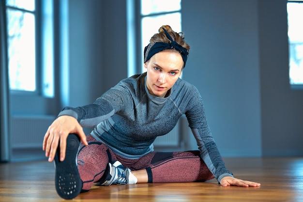 Jonge mooie vrouw in sportkleding die het uitrekken doen zich terwijl het zitten op de vloer voor venster bij gymnastiek