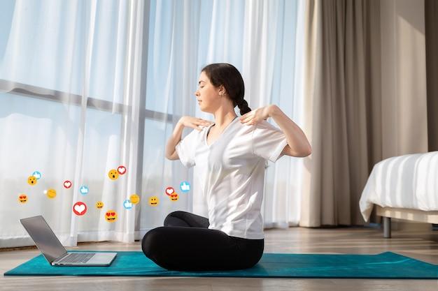 Jonge mooie vrouw in sportkleding die yoga live online doet. binnen. emoticons en emoji's vliegen rond de laptop. zijaanzicht. het concept van sociale netwerken, online training en bloggen.