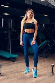 Jonge mooie vrouw in sportkleding in een sportschool