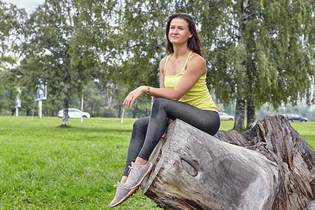 Jonge mooie vrouw in sportkleding zit overdag op boom in openbaar park.